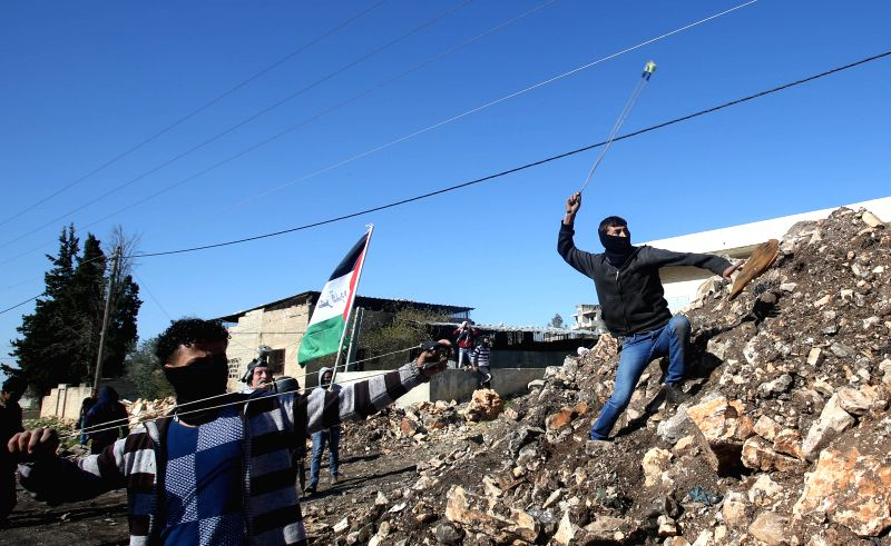 A Palestinian protester throws stones at Israeli soldiers during a protest against the expanding of Jewish settlements in Kufr Qadoom village near the West Bank city ...