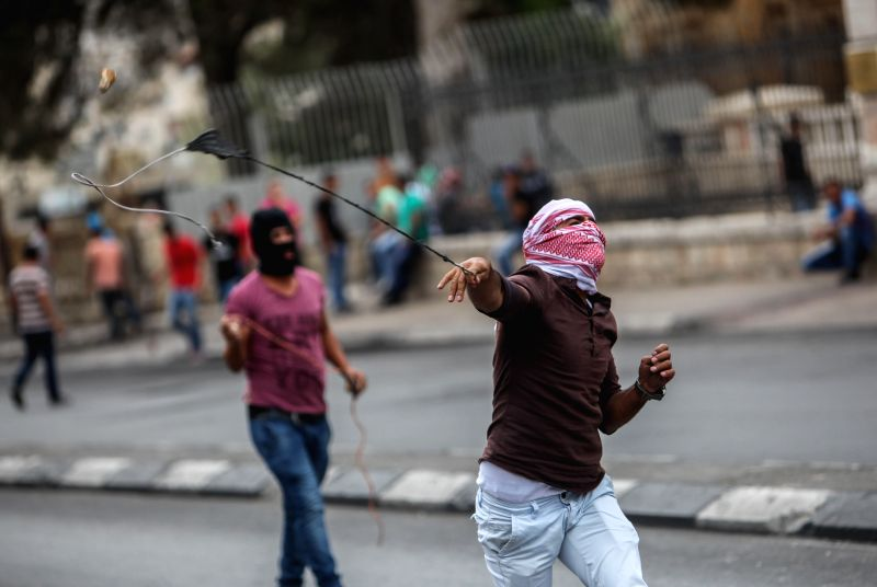 A Palestinian protester uses a slingshot to throw stones towards Israeli soldiers during clashes in the West Bank city of Bethlehem, on Oct. 23, 2015. At least 96 ...