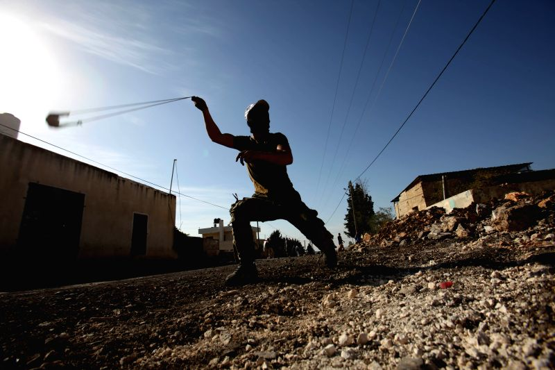 A Palestinian protester uses a slingshot to throw stones towards Israeli soldiers during a protest against the expanding of Jewish settlements in Kufr Qadoom village ...
