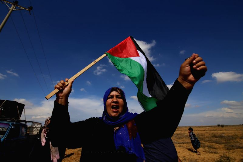 A Palestinian woman waves national flag during an anti-Israel protest near the border between Israel and the southern Gaza Strip on Oct. 28, 2015. Since early October, ...