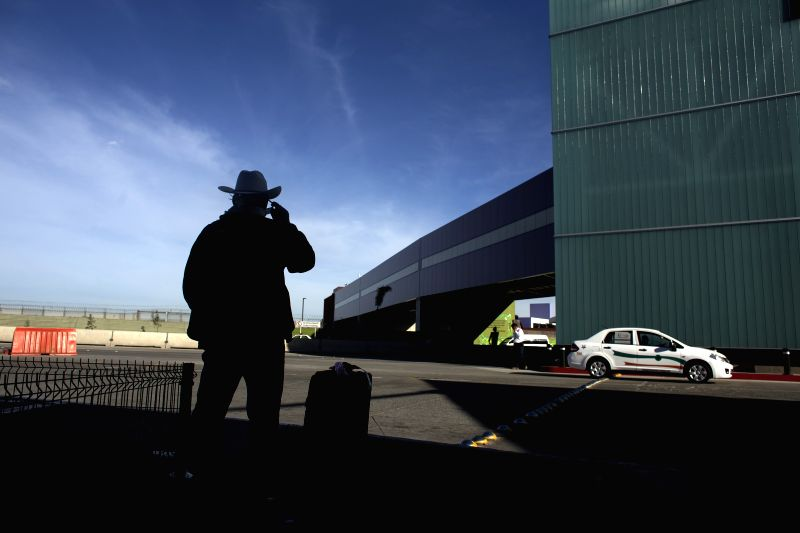 A passenger stands in front of the international bridge known as Cross Border Xpress (CBX) at the Tijuana airport, northwest Mexico, Dec. 9, 2015. The CBX links San ...