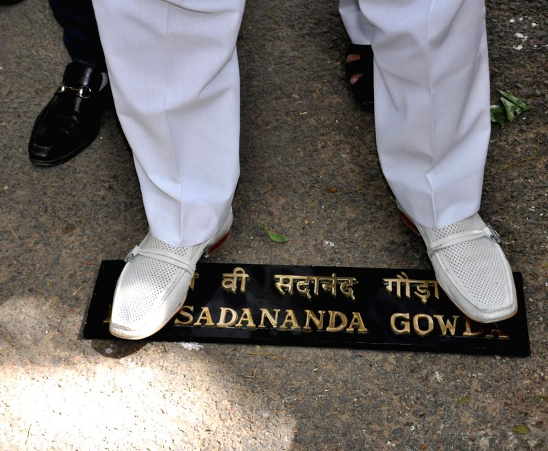A person demonstrating against Rail budget 2014-15 outside the residence of Union Railway Minister D.V. Sadananda Gowda stamps on the minister's name plate in New Delhi on July 8, 2014. - D.