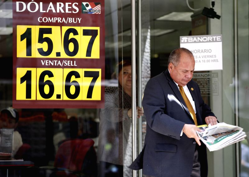 A person walks in front of a board that shows the exchange rate of the Mexican peso against the U.S. dollar, in Mexico City, capital of Mexico, Aug. 18, 2015. ...