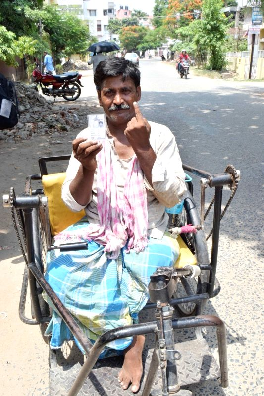 A physically challenged man shows his forefinger marked with phosphorous ink after casting vote during Patna Municipal Corporation elections on June 4, 2017.