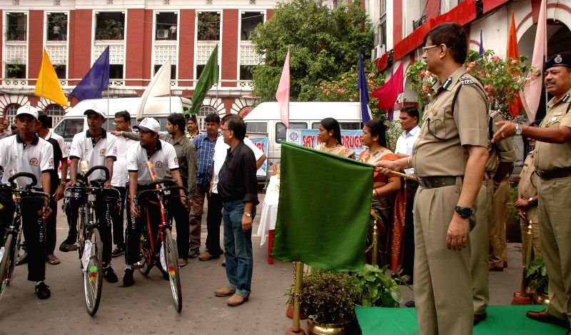 A police official flags-off an anti-drug cycle rally from Kolkata Police Headquarters in Kolkata on June 20, 2014.