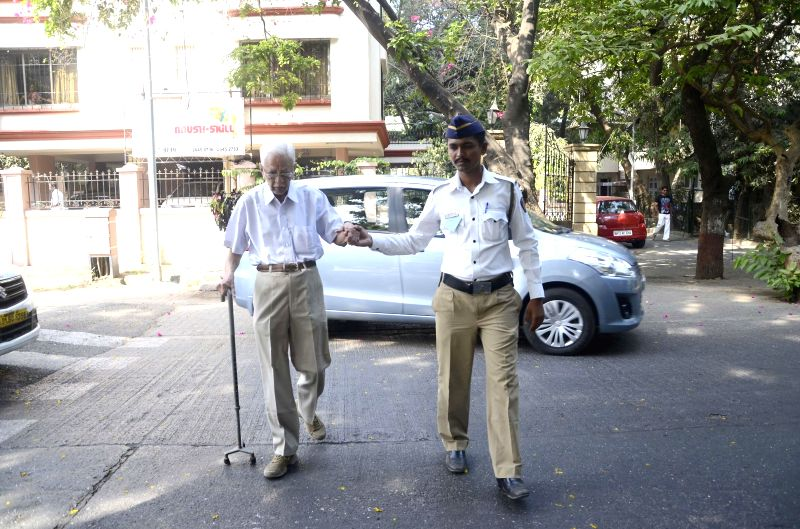 A police personnel helps an elderly gentleman to reach a polling booth during the sixth phase of 2014 Lok Sabha Polls  in Mumbai on April 24, 2014.