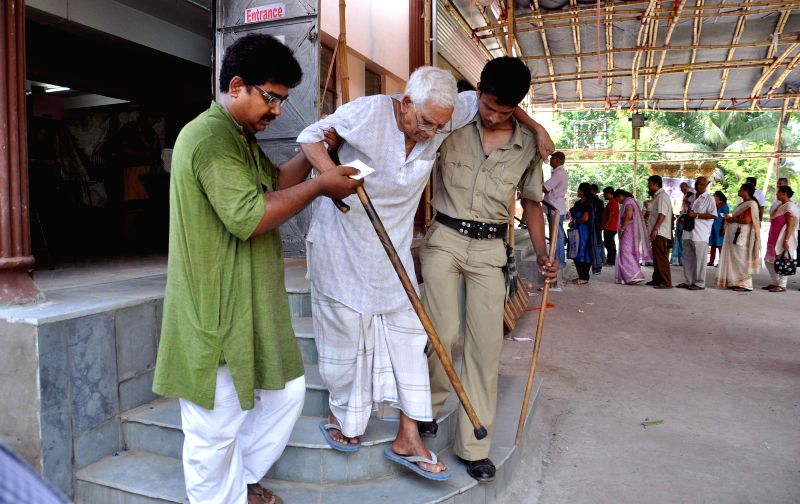 A policeman and a civilian assist an elderly gentleman in climbing down stairs at polling booth after casting his vote  during the ninth phase of 2014 Lok Sabha Polls in Kolkata on May 12, 2014.