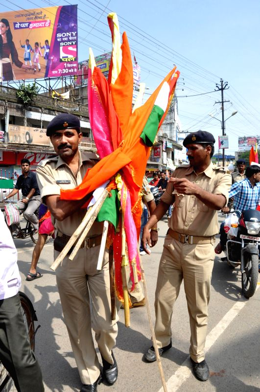 A policeman holds religious flags seized from bandh supporters during Ranchi Bandh called by Hindu outfits in support of Tara Sahdeo, a national rifle shooting woman gold medallist who has alleged ...