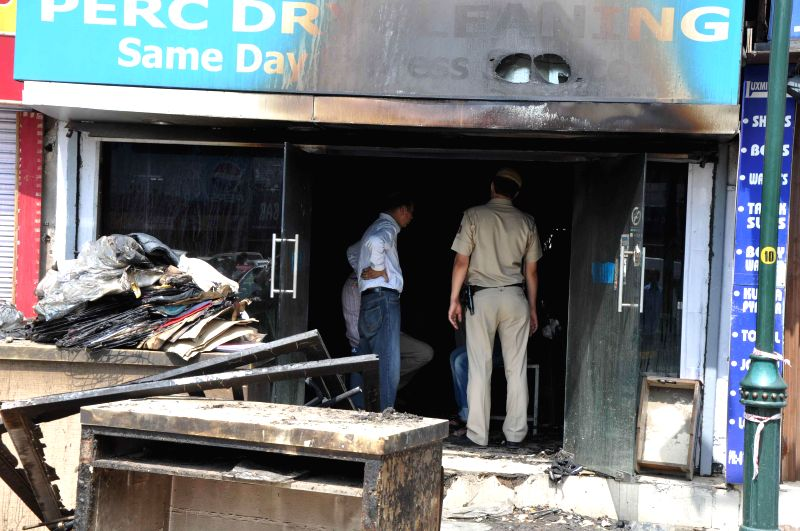 A policeman inspects the shop where a fire broke out at Bengali Market in Mandi House of New Delhi on April 25, 2014.