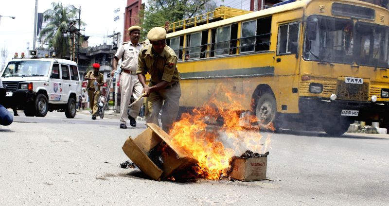 A policeman tries to douse a fire lit-up by Asom Gana Parishad (AGP) activists during a 12-hour Assam bandh, called to protest against recent violence in Golaghat of Assam, in Guwahati on Aug 21, ...