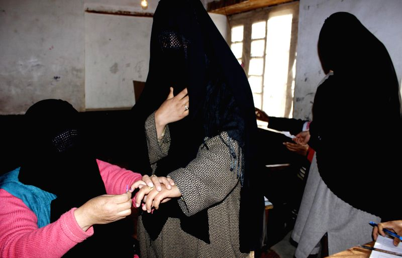 A polling officer wearing a hijab applies phosphorous ink on the forefinger of  a voter at a polling booth during the sixth phase of 2014 Lok Sabha Polls in Anantnag Lok Sabha constituency of Jammu ..