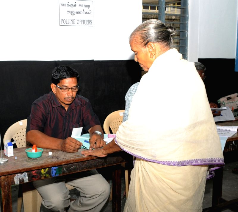 A polling official administering indelible ink to a voter, at a polling booth, during the Puducherry Assembly Election, on May 16, 2016.