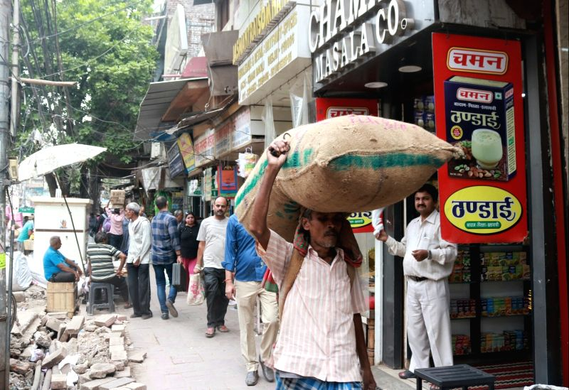 A porter carries load on his head at Khari Baoli whole sale market near Chandni Chowk, in New Delhi. (File Photo: IANS)