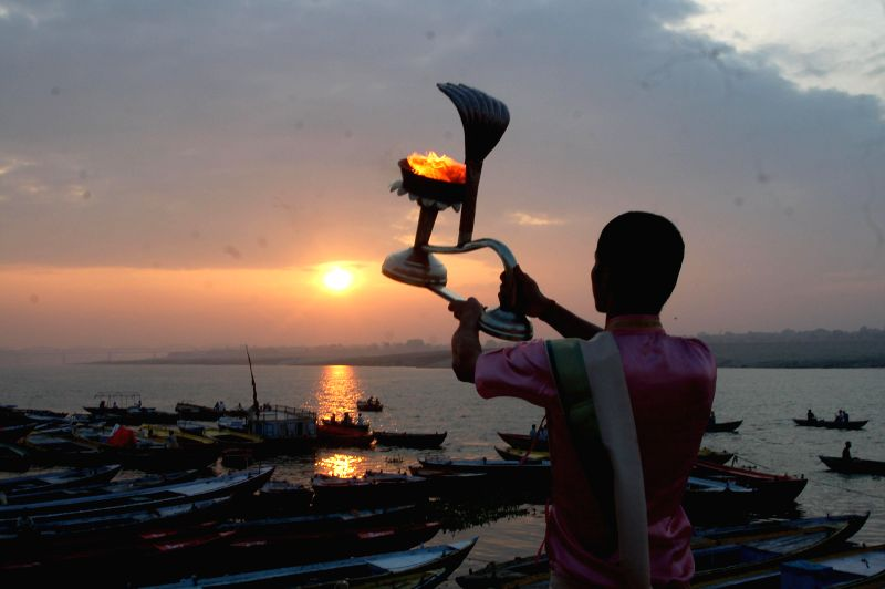 A priest conducts morning aarti on the banks of Ganga river in Varanasi on Sept 3, 2014.