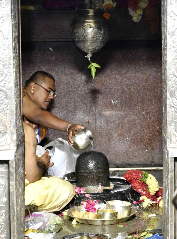 A priest pours water and milk over the Shiv Linga as he perform rituals on the occasion of Maha Shivaratri at Keesaragutta temple in Medchal-Malkajgiri district in Telangana on Feb 13, ...
