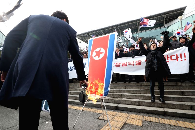 A protester burns a North Korean national flag as a conservative group holds a rally in front of Seoul Station on Jan. 22, 2018, to voice objection to the North's participation in next month's ...