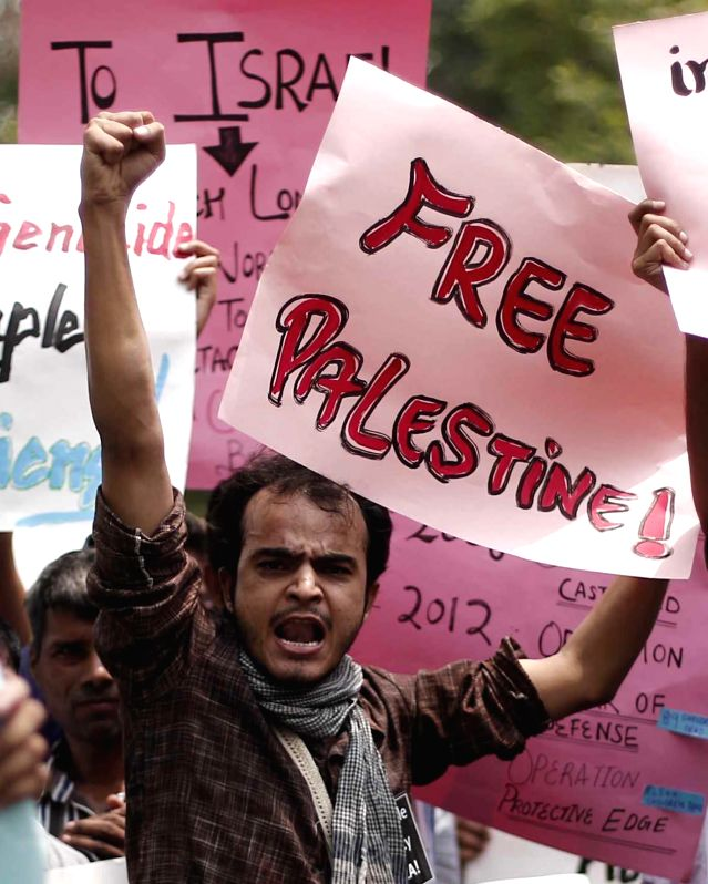 A protester holds a placard as he shouts slogans against Israeli attacks on Gaza in New Delhi on July 13, 2014.