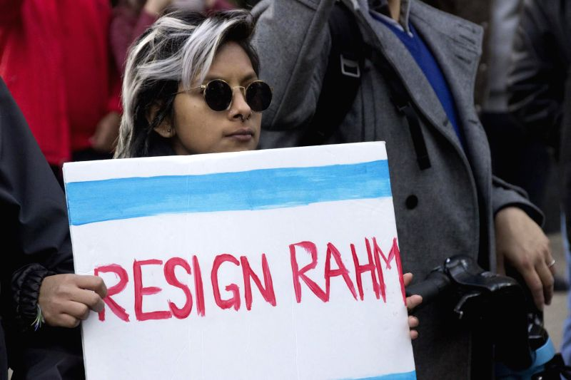 A protester holds a placard during a protest in Chicago, the United States on Dec. 9, 2015. More than 300 protesters marched through downtown Chicago on Wednesday, ...