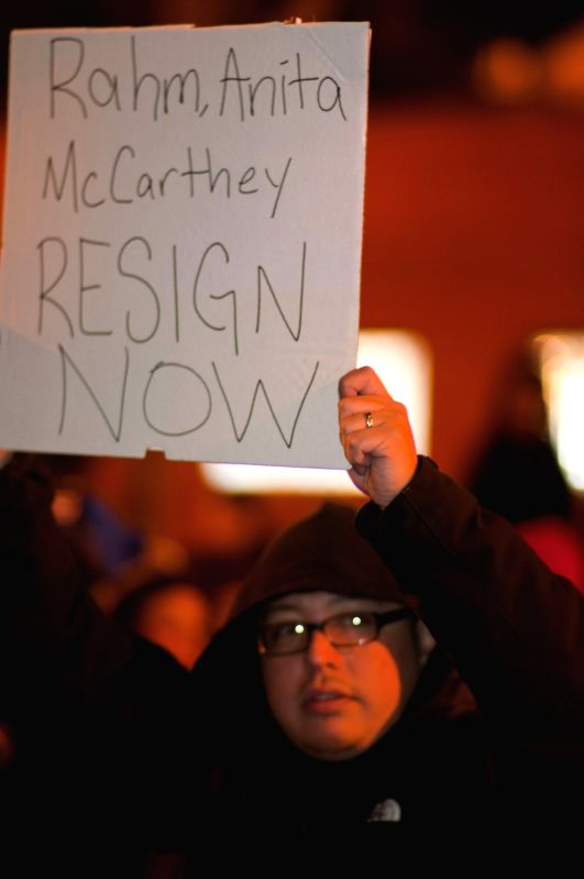 A protester holds up a sign during a protest against the shooting in Chicago, the United States, on Nov. 24, 2015. Police released a video on Tuesday showing the ...