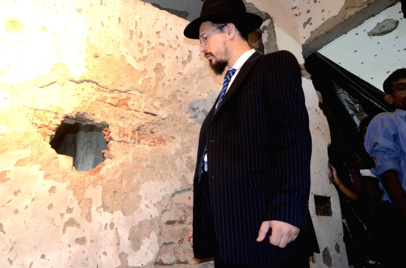 A Rabbi looks at the bullet marks in the walls of Chabad Center at Nariman House in Mumbai after it was reopened on Aug 26, 2014.
