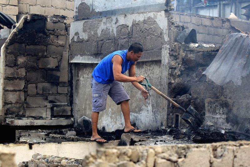 A resident looks for his belongings from burnt houses after a fire at a slum area in Manila, the Philippines, Dec. 5, 2015. More than 500 shanties were razed in the ...
