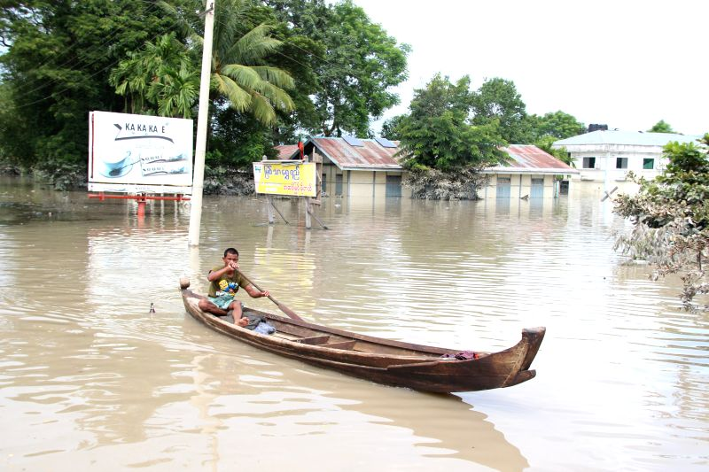 A resident paddles his boat in a flooded area in Kalay township of Sagaing Region, Myanmar, Aug. 3, 2015. Heavy monsoon rains have left at least 47 people dead and ...