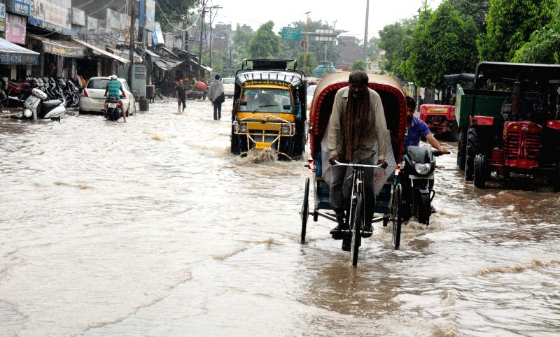A rickshaw puller struggles through flooded streets of Amritsar after heavy showers in Amritsar on Sept 4, 2014.