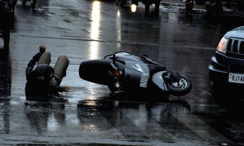 A rider slips and falls on road during rains in Jaipur, on May 31, 2017.