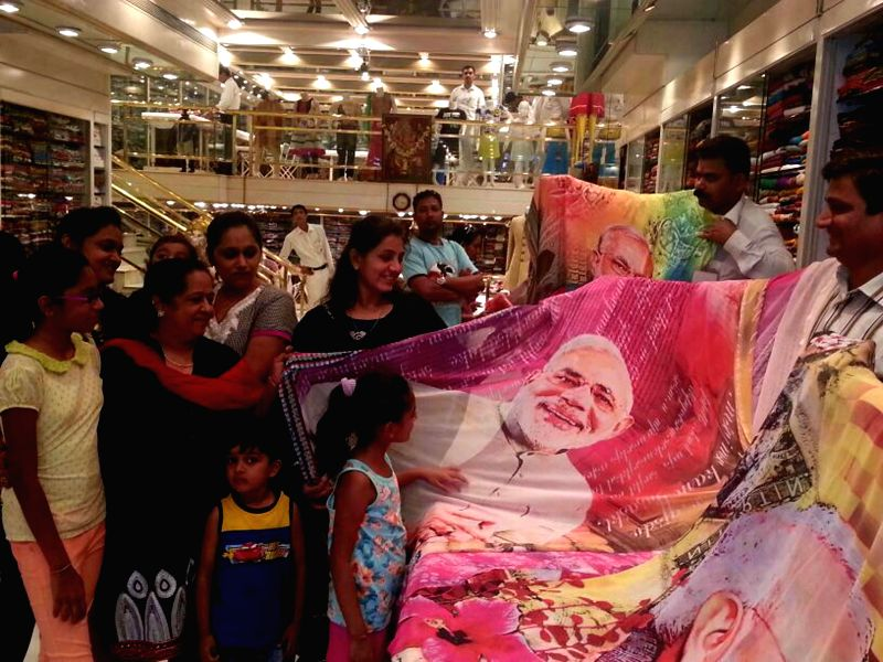 A salesman shows a saree with a picture of BJP Prime Ministerial candidate and Gujarat Chief Minister Narendra Modi printed on it in Mumbai on May 15, 2014.