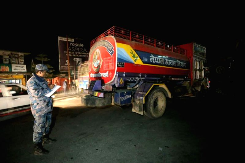 A security personnel notes down the record of fuel tankers of Nepal Oil Corporation (NOC) which arrived in Kathmandu valley after receiving the petrol assisted by ...
