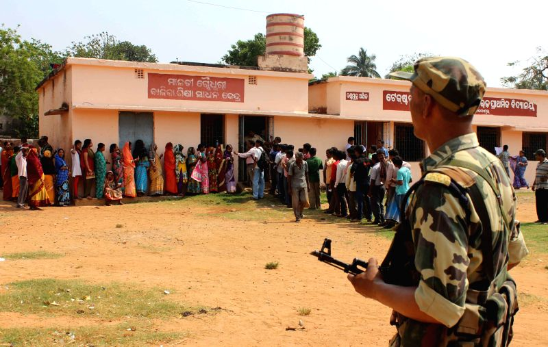 A security personnel stands on guard as people queue-up to cast their votes at a polling booth during the fifth phase of  2014 Lok Sabha Polls in Bhubaneswar on April 17, 2014. (Photo : Arabinda ...