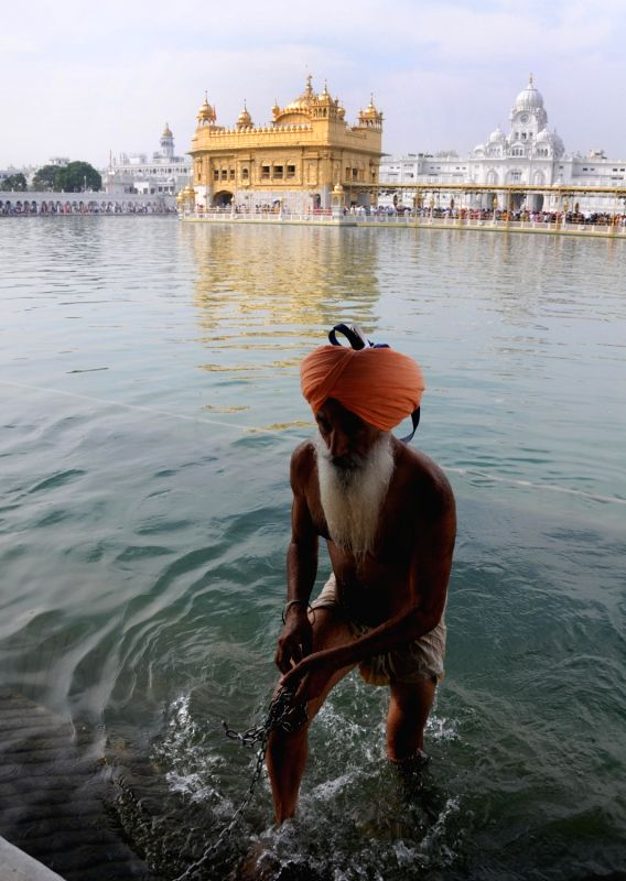 A Sikh devotee comes out after taking a holy dip in the pond at Golden Temple during Baisakhi celebrations, in Amritsar on April 14, 2018.