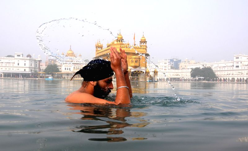 A Sikh devotee takes a dip at the holy sarovar of the Golden Temple on the 350th birth anniversary of Guru Gobind Singh in Amritsar, on Dec 28, 2014.