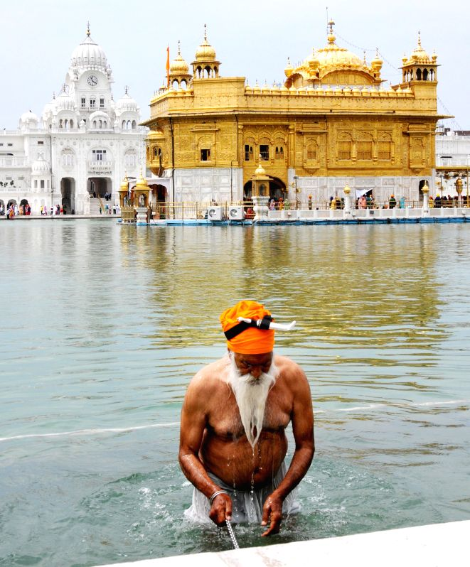 A sikh devotee takes a holy dip at the Golden Temple on 393rd birth anniversary of the ninth Sikh Guru Teg Bahadur in Amritsar on April 18, 2014.