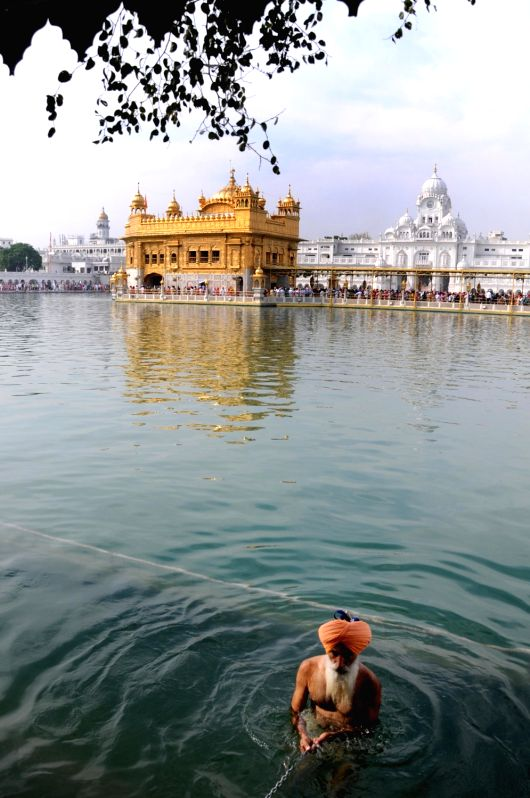 A Sikh devotee takes a holy dip in the pond at Golden Temple during Baisakhi celebrations, in Amritsar on April 14, 2018.