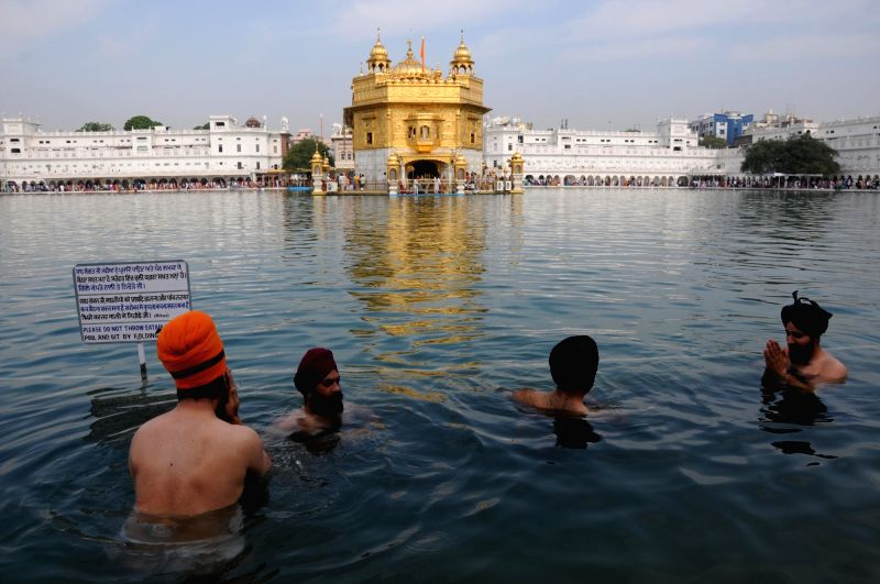 A Sikh devotees takes a holy dip in the pond at Golden Temple during Baisakhi celebrations, in Amritsar on April 14, 2018.
