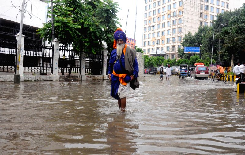 A Sikh nihang wades through flooded streets of Amritsar after heavy showers in Amritsar on Sept 4, 2014.