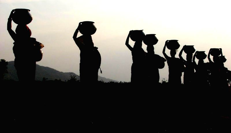 A silhouette of women carrying water pots from Daya river in the outskirts of Bhubaneswar. Women are forced to walk down to the river to fetch water due to acute water scarcity that prevails in the ..