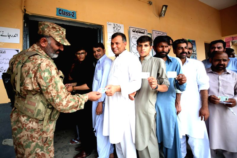 : A soldier checks the identity card of a voter at a polling station during the general elections in Rawalpindi, Pakistan, on July 25, 2018. Pakistan held the ...