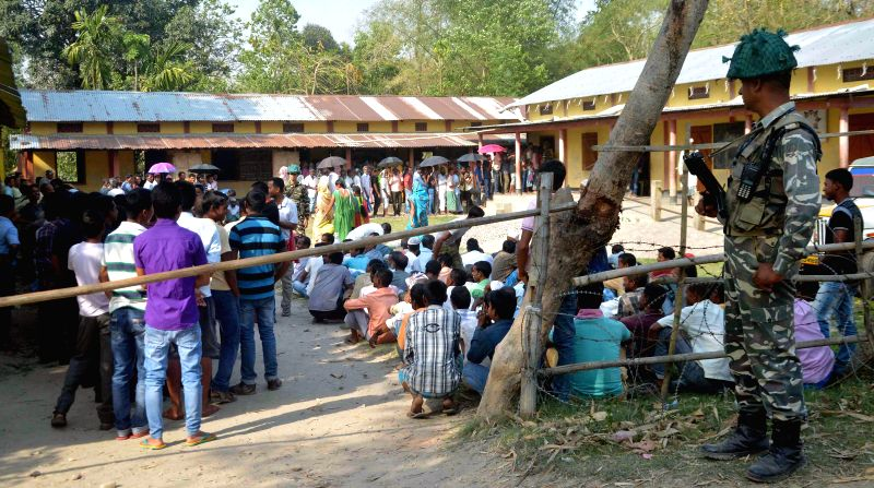 A soldier stands guard as women queue-up to cast their votes at a polling booth during the sixth phase of 2014 Lok Sabha Polls in Kokrajhar of Assam on April 24, 2014.