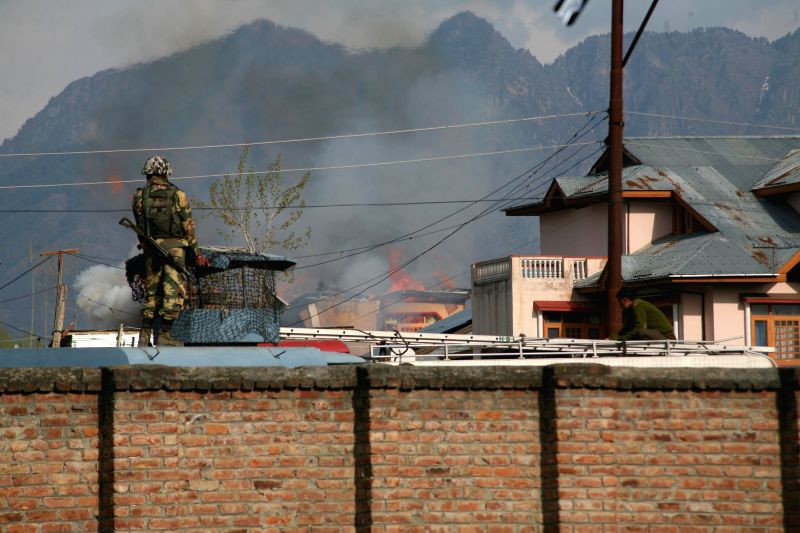 A soldier stands on a wall during an encounter between militants and the security forces which lasted for around 20 hours in Ahmad Nagar, 10 km from Srinagar on April 14, 2014. Two militants were ...