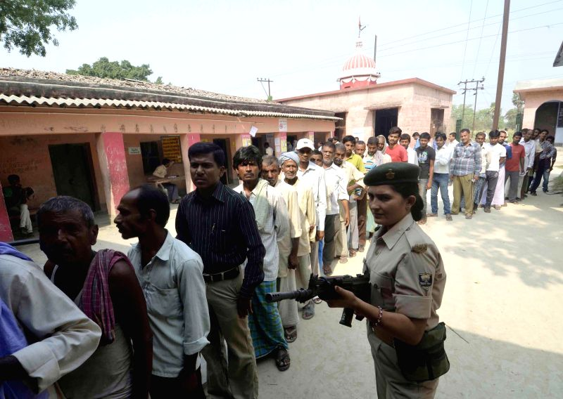 A soldier stands on guard as people queue-up to cast their votes at a polling booth during the seventh phase of  2014 Lok Sabha Polls in Howrah of west Bengal on April 30, 2014.