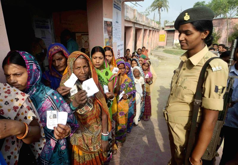 A soldier stands on guard as women queue-up to cast their votes at a polling booth during the seventh phase of  2014 Lok Sabha Polls in Samastipur of Bihar on April 30, 2014.