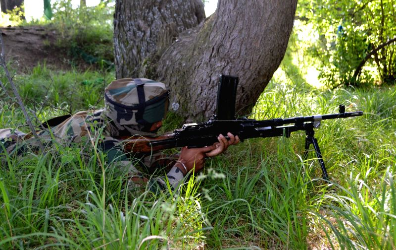 A soldier takes position during an encounter with militants at Zonrishipora (Chowkibal) village of Kupwara district in Jammu and Kashmir on May 17, 2016. One militant was killed.