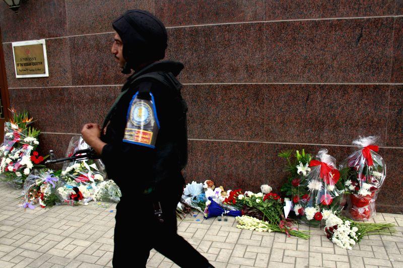 A soldier walks by the Russian Embassy in Cairo outside which flowers are put for victims of a Russian plane crashing in Egypt on Saturday, in Cairo, Egypt, on Nov. 1, ...
