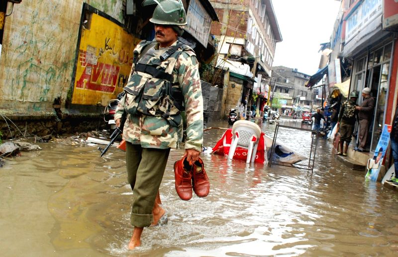 A soldier walks on a waterlogged street of Srinagar after rains lashed the city on April 6, 2016.