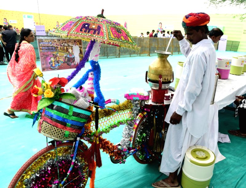 A tea seller prepares tea on a decorated bicycle during Rajasthan Digifest 2018, in Bikaner on July 25, 2018.