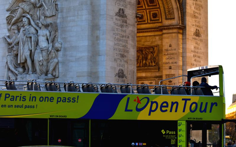 A tour bus with few passengers drives on the Place Charles de Gaulle in Paris, capital of France, on Nov. 18, 2015. A large number of foreign tourists cancelled or ...