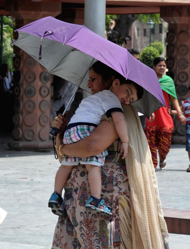 A tourist use a an umbrella as a shield against scorching sun at Jallianwala Bagh in Amritsar on May 4, 2014.