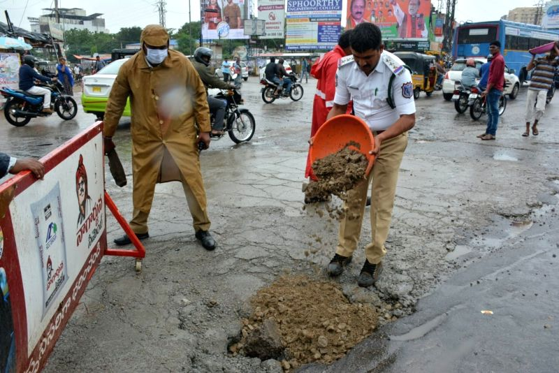 A traffic personnel fills up a pothole after heavy rains lashed Hyderabad on July 12, 2018.